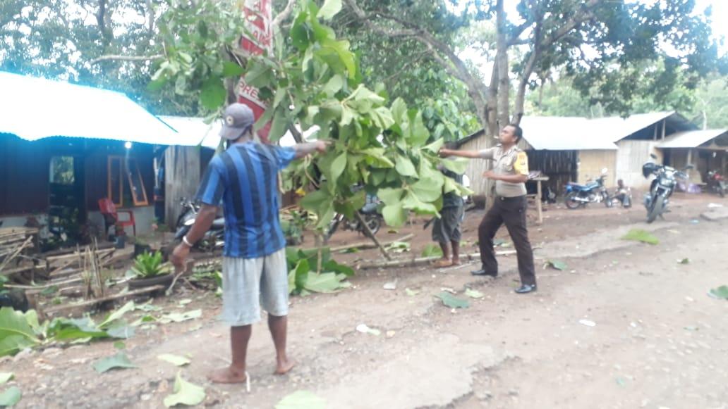 Brigpol Yohanes Namang membantu menebang pohon di pekarangan rumah warga